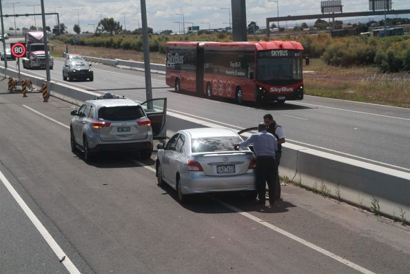 SkyBus articulated bus #81 passes a broken down taxi on the Tullamarine Freeway at Essendon Airport