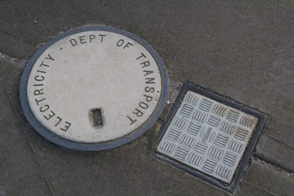 'Department of Transport' and 'VicRoads' branding on manholes at a SmartBus stop