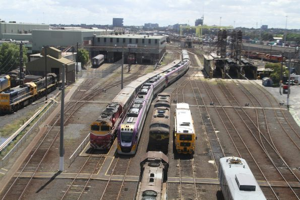 Stabled V/Line trains beside a ballast tamper at South Dynon