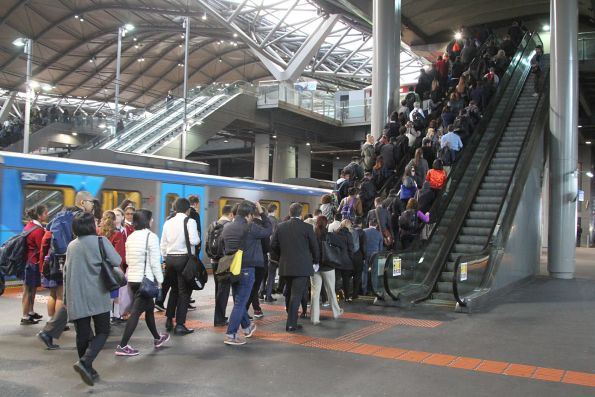 Crowd of passengers queue to use the escalator at Southern Cross platform 13