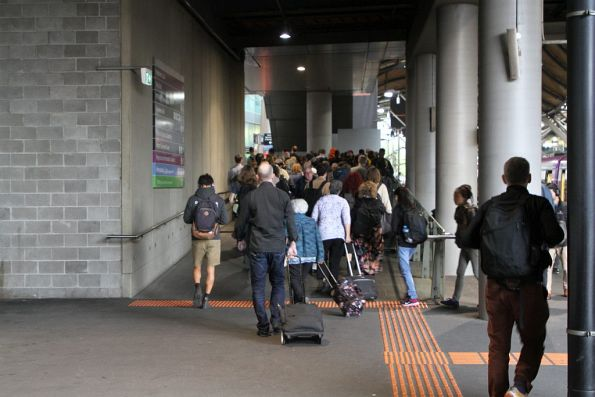 Long queue of passengers waiting to pass through the two myki gates at the exit of Southern Cross platform 1