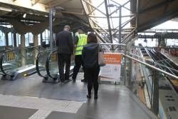 Security staff restart the escalator to Southern Cross platform 11 and 12 after it shutdown