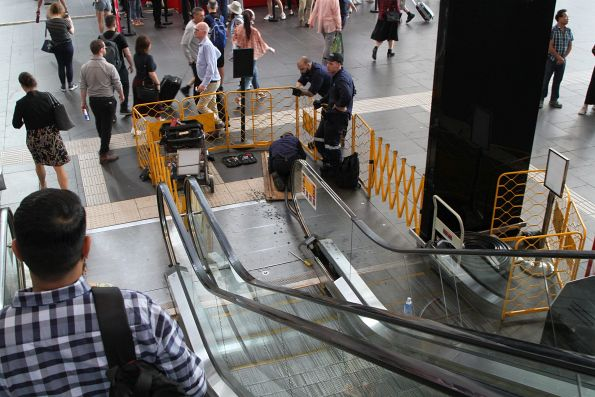 Repairing a broken down escalator at the main entrance in morning peak