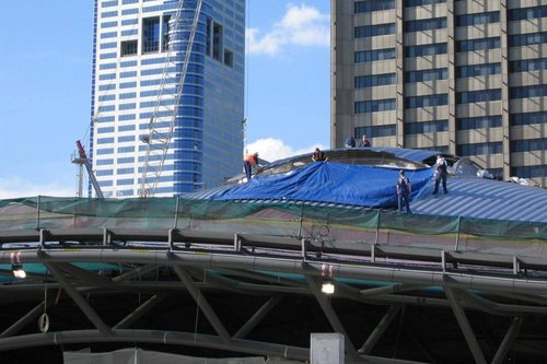 Workers busy at work cladding the roof