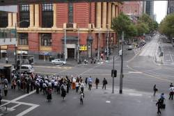 Morning commuters wait for the traffic lights at the corner of Spencer and Bourke Streets