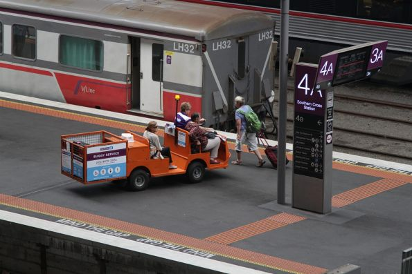 Travellers Aid buggy delivers a pair of passengers to their train
