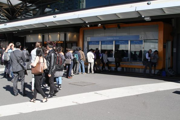 Long line of passengers waiting for tickets at the Bourke Street booking office at Southern Cross
