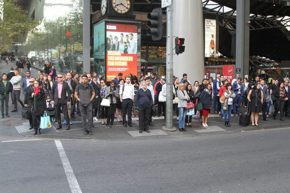 A hundred pedestrians are forced to wait, despite no traffic on Spencer Street