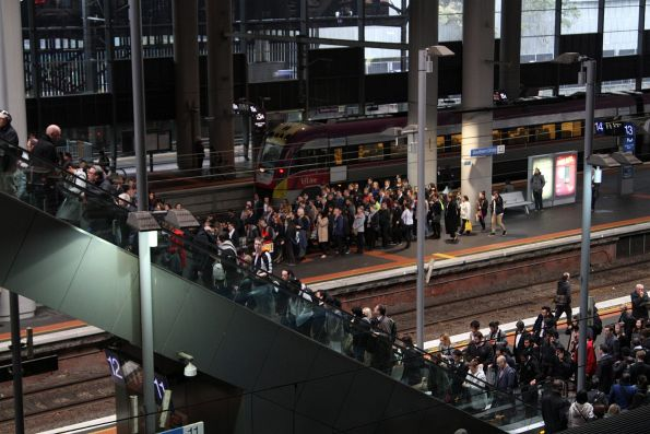 Crowd of commuters fill the platforms, queuing for the escalators at Southern Cross Station