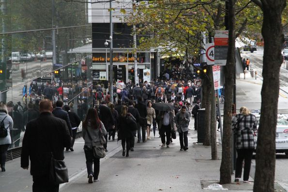Crowd of commuters cross at the corner of Spencer and Collins Street