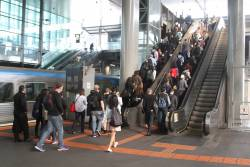 Crowd of passengers exit Southern Cross platform 13 and 14