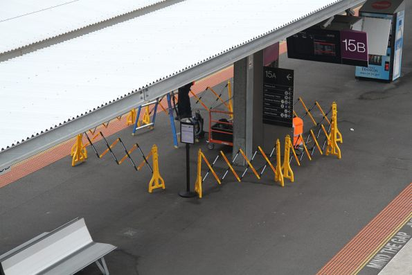 Maintenance staff work on the next train displays at Southern Cross platform 15 and 16
