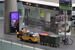 Electric buggy leads a train of rubbish bins around the concourse