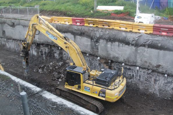 Excavator breaking up rock in the cutting at the up end of Ginifer station