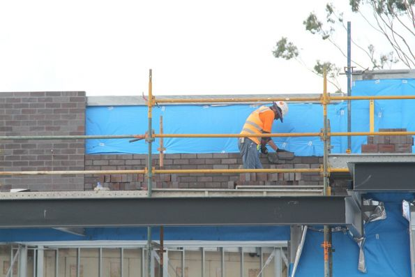 Bricklayer at work outside the new railway station shops at St Albans
