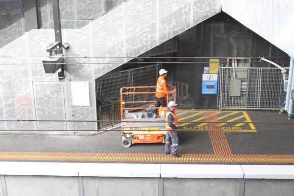 Safewroking staff accompany a scissor lift as it drives along the platform