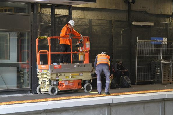 Safeworking staff use a tape measure to check if the scissor lift is far enough from the edge of the platform