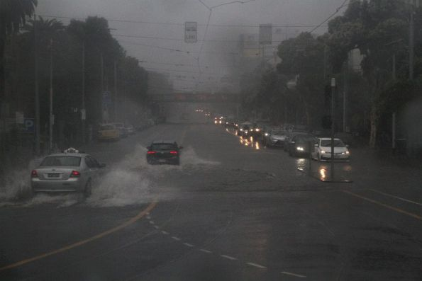 Flood waters cover the tram tracks at Commercial Road and St Kilda Road