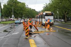 Yarra Trams staff clear fencing dislodged by floodwater off the St Kilda Road tram tracks at Coventry Street