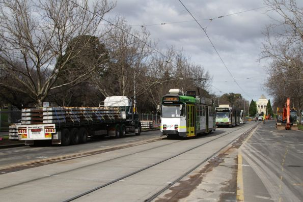 Southbound trams on St Kilda Road passes a delivery of tramway sleepers for the upcoming works