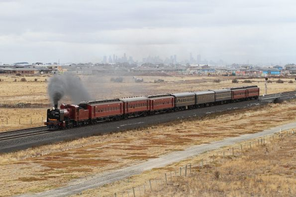 K190 leads the down train past the Melbourne CBD skyline at Tarneit