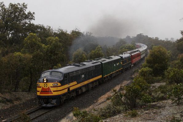 After crossing a late running up pass, S313 leads the train past the Werribee Gorge towards Ingliston