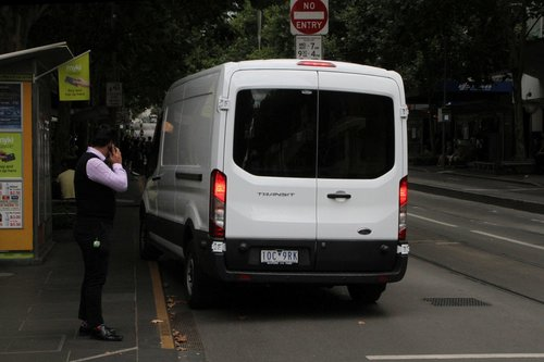 Van driver heads past waiting pedestrians to drive down the bike lane