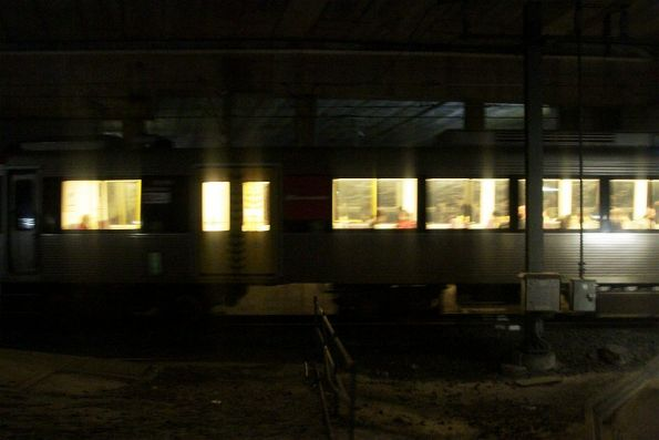 Passing a suburban train in the dark, beneath the offices that occupy the deck over Central station