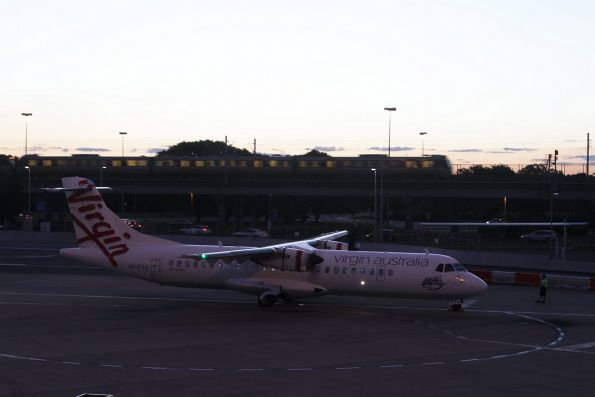 Train bound for Domestic station passes a Virgin Australia ATR-72-500 turboprop