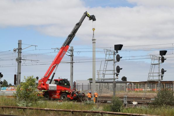 Erecting additional overhead stanchions at the up end of Sunshine station