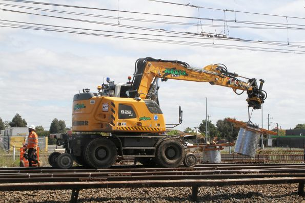 Hi-rail excavator transports a pile cap to a freshly bored overhead stanchion hole