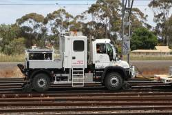 John Holland hi rail Unimog tows a 'train' of wagons loaded with overhead gantries at Sunshine