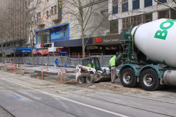 Moving wet cement around at the Swanston and Collins Street platform stop