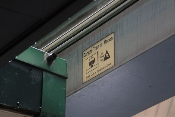 'Danger Train in Motion' sign beside a building veranda
