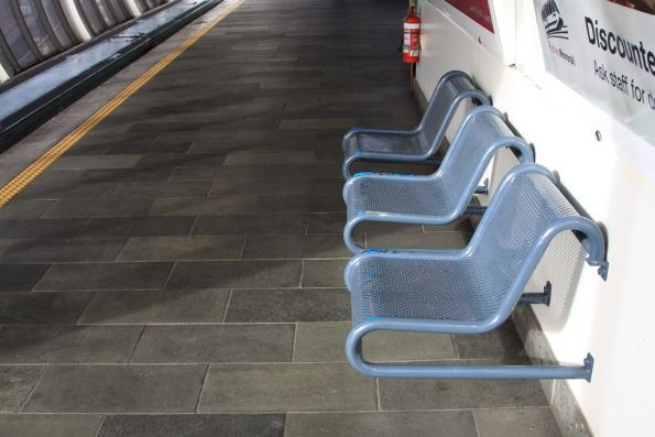 Wall mounted metal seats, as seen at all of the original Monorail station