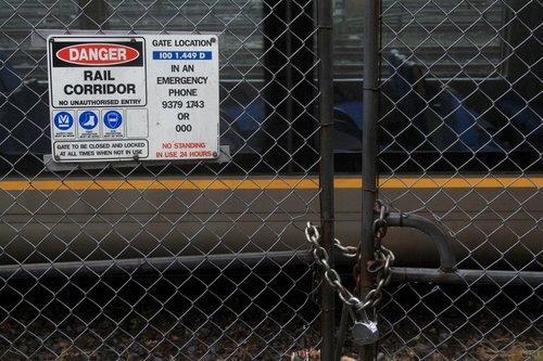 'Danger Rail Corridor' sign on a locked gate