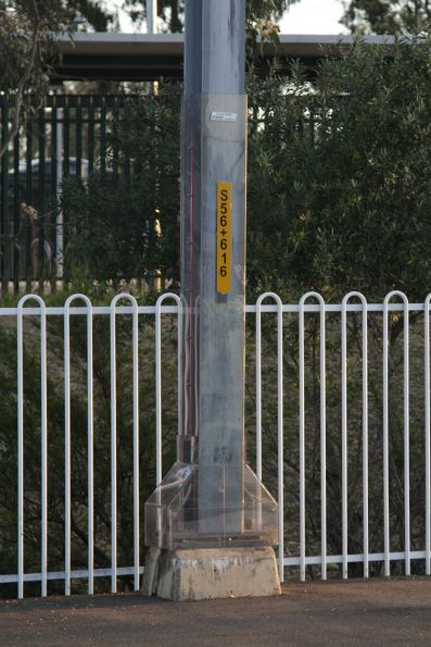 Overhead stanchion insulated from the adjoining metal fence by clear perspex