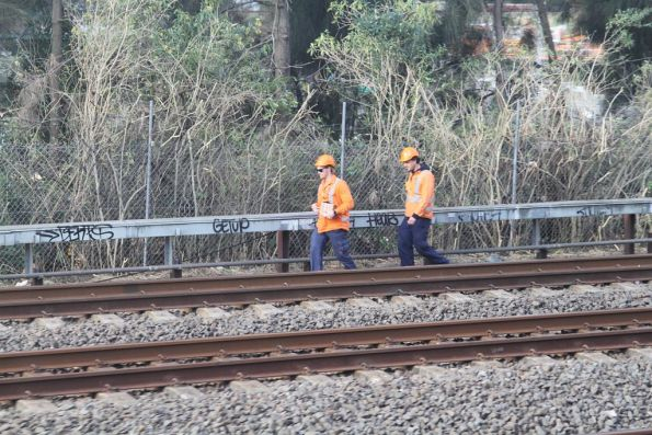 Track staff work beside the line at Strathfield