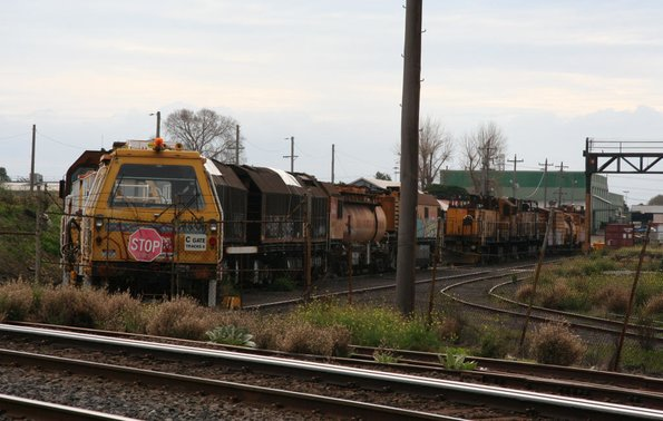 Ballast tamper in front of rail grinders RG9 and RG7 at Spotswood