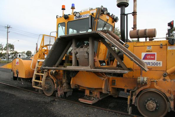 Plough for moving ballast on the shoulder, stowed in the up position