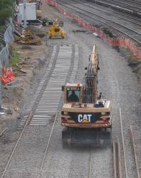 Excavator on the move, laying new track at Southern Cross