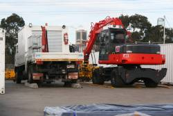 Hi-rail truck up on concrete sleepers, beside an excavator with a tamper attachment