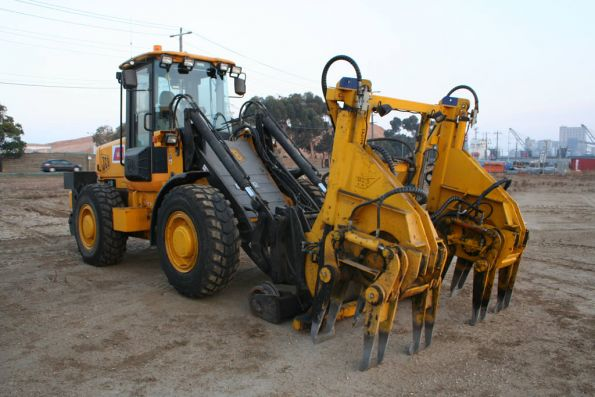 Ballast tamper attachment on a front end loader