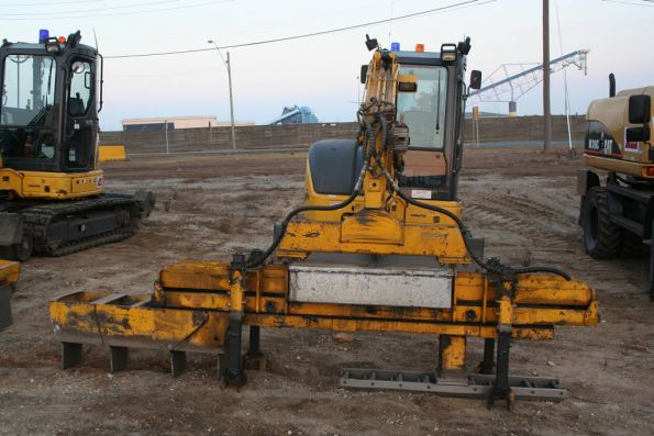 Excavator with an attachment to clear out the ballast for new sleepers to be put in