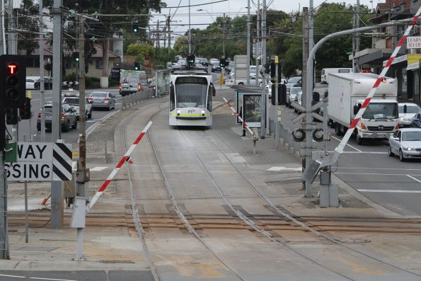 Boom gates go down on Burke Road as tram D1.3515 arrives at Gardiner station