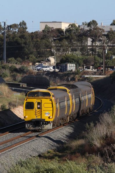 With the former Mitsubishi factory in the background, a 3-car Jumbo heads towards Noarlunga