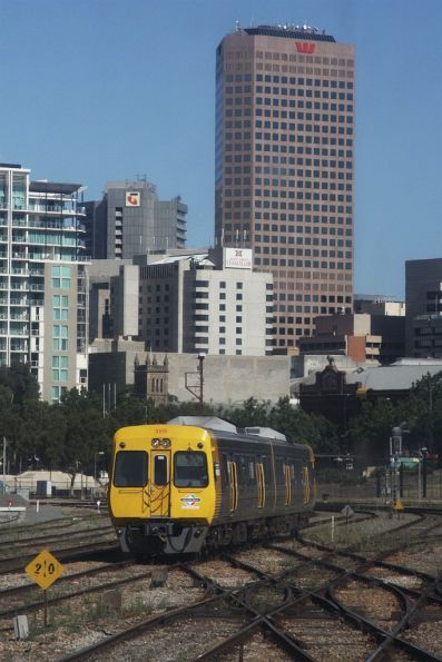 Comeng 3109 and classmate depart Adelaide station with the CBD skyline behind