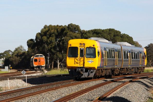 One heads in, the other heads out: a 3100 class set passes an inbound Jumbo at Torrens Junction