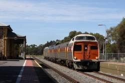 Jumbo 2115 leads a mixed liveried set running express through North Adelaide on the down