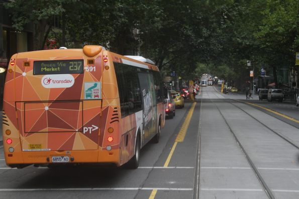 Transdev bus stuck in eastbound traffic on Collins Street as trams glide past